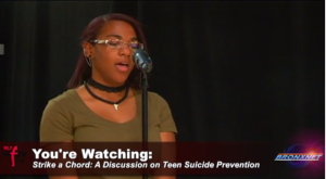 Student Cleopatra Green asks the expert panel a question regarding teen suicide during the Strike A Chord Campaign panel discussion.