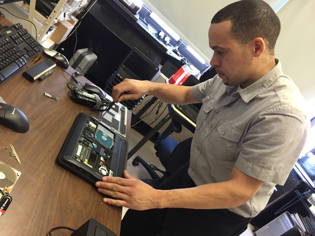 Computer technician Juan Rodriguez gets an inside look at a laptop, to try and figure out what's wrong.