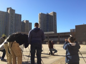 Co-Op City serves as the backdrop as students learn to assemble and use telescopes during their astronomy class.