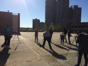 The sun casts long shadows behind students as they practice setting up and focusing brand new telescopes.