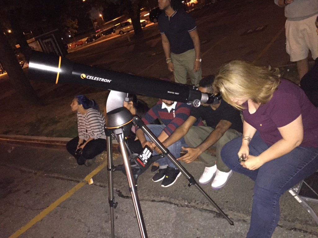 Earth Science and Astronomy teacher Ms. Robbins double-checks the telescope's alignment during Sunday's eclipse.