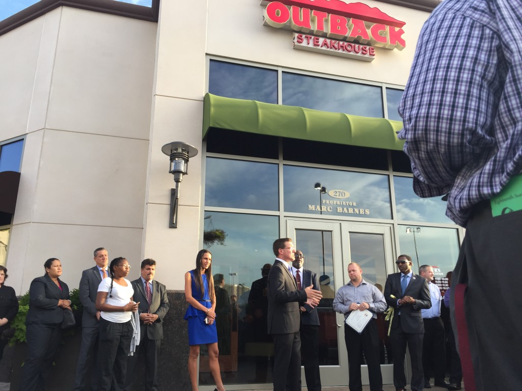 Media Teacher Mr. Roush makes brief remarks outside the new Outback Steakhouse during a ribbon cutting ceremony on Monday.