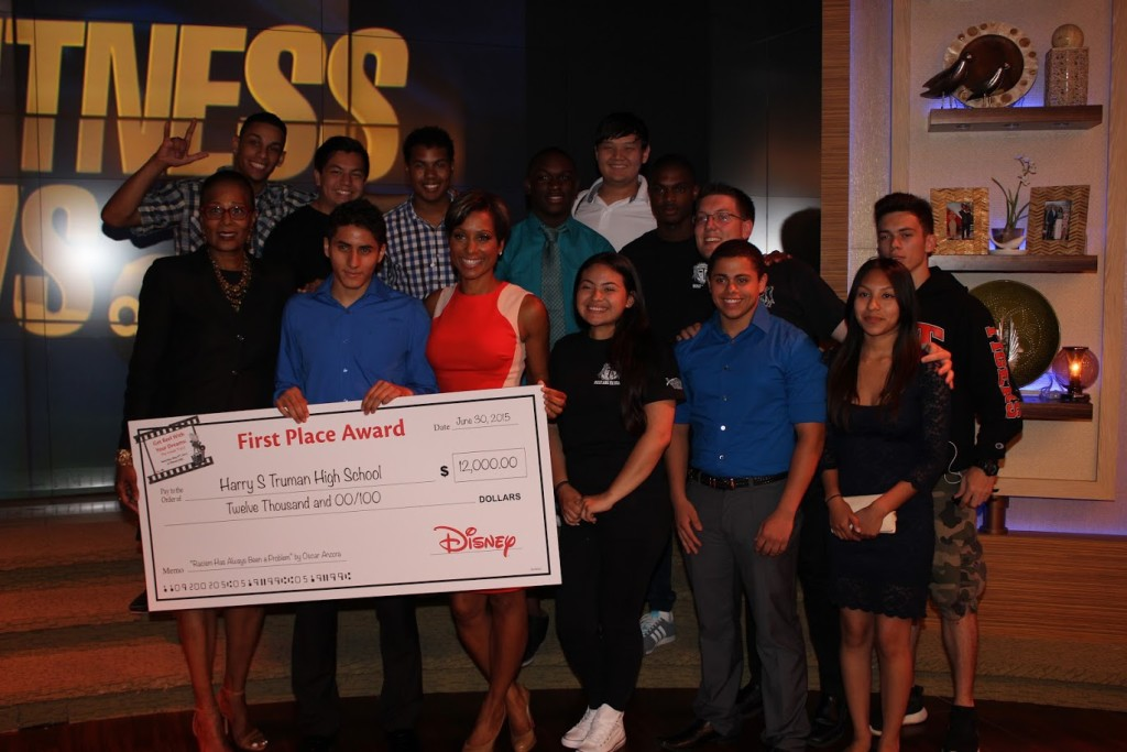 Oscar Anzora receives his award check from ABC 7 Eyewitness News anchor Sade Baderinwa, surrounded by his classmates.
