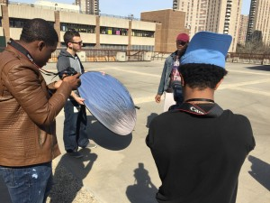 Russo demonstrates using a reflector while sophomore Abel Zewde shoots.