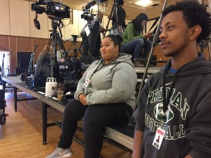 (l to r) Eliza Perez and Abel Zewde wait on the media risers for Hillary Clinton's arrival.