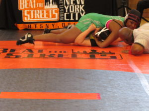 Senior Shaniece Hunter grins as she nearly pins her opponent at a recent Beat the Streets wrestling event.