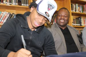Jefferson cracks a smile while signing his commitment letter as his father, Wayne, looks on. (Photo by Abel Alexander)